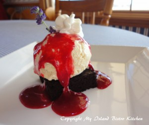 Homemade Lavender Ice Cream Served on a Brownie and Drizzled with Raspberry Coulis
