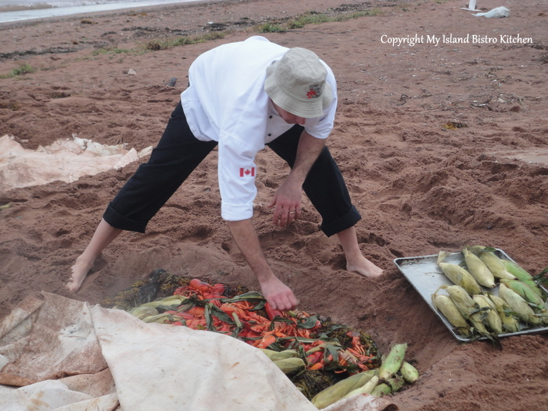 Chef Andrew Nicholson removes the cooked lobster and corn from the cooking pit