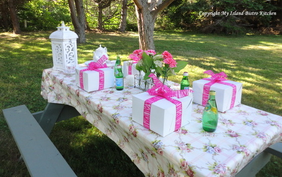 White picnic lunch boxes tied with bright pink ribbon