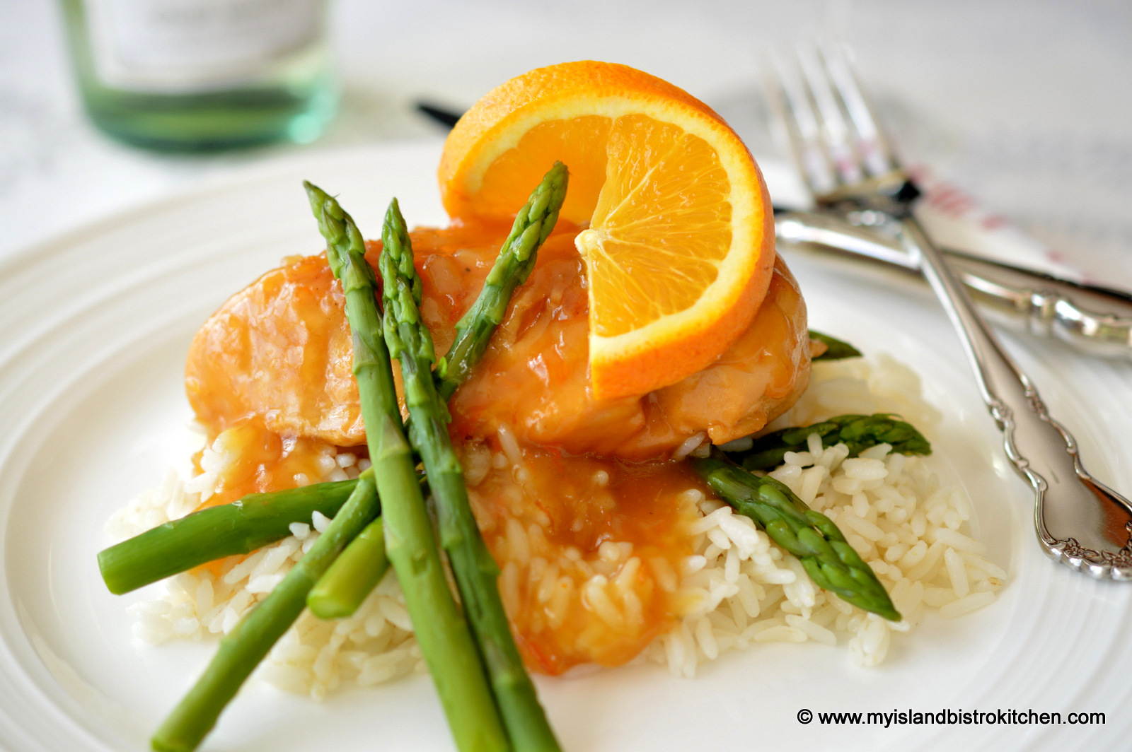 Maple-Orange Sauced Chicken Breast on top of a bed of white rice served with green asparagus and an orange wheel