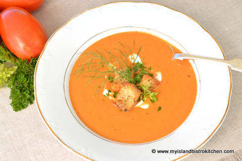 Bowl of Tomato Soup topped with croutons and fresh herbs