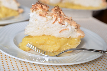 Slice of coconut cream pie with mile high meringue