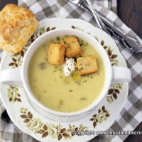Potato Leek Soup garnished with croutons and a sprinkle of parsley in white bowl alongside a homemade biscuit