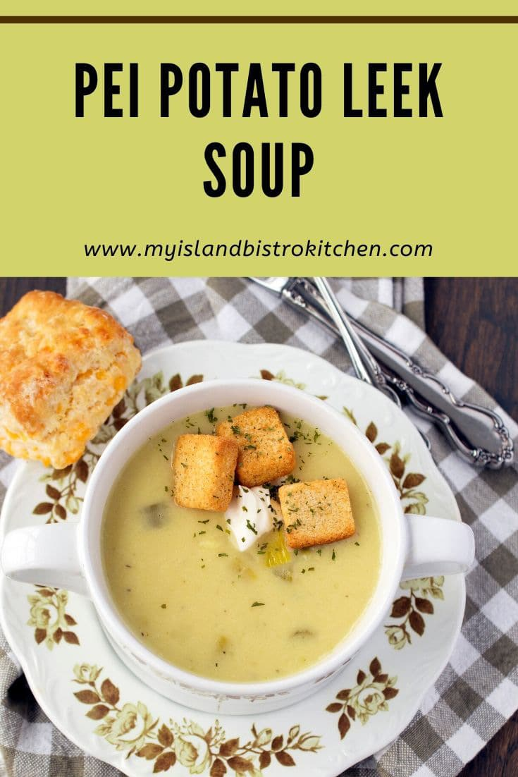 white soup bowl filled with creamy potato leek soup topped with croutons and a dollop of sour cream