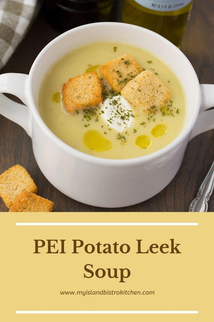 white bowl filled with creamy potato leek soup topped with croutons and a dollop of sour cream