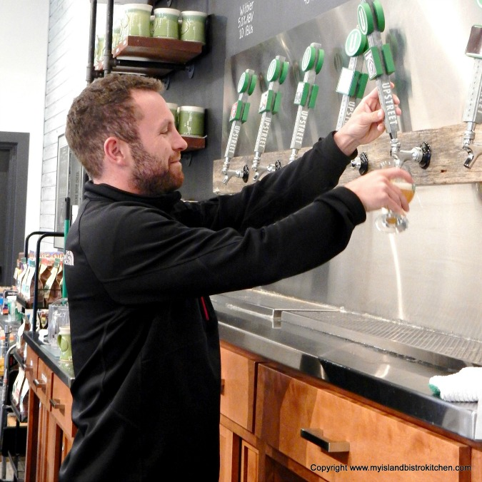 Joey Seaman pours a glass of beer in Upstreet Craft Brewing's Taproom