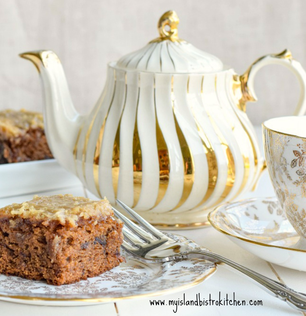 Gluten-free Queen Elizabeth Cake on gold and white plate with matching cup and saucer and a gold and white teapot in the background