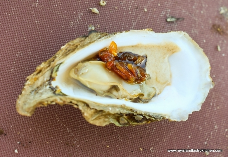 PEI Oysters hot off the grill and served with black garlic cream sauce and bacon jam
