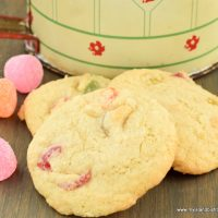 Three Gumdrop Cookies in front of an antique flour sifter