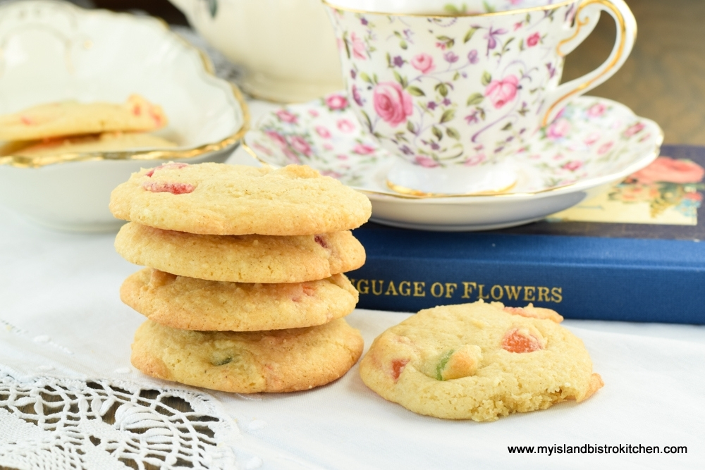 Stack of Gumdrop Cookies in front of a pink and purple china cup and saucer sitting on a book