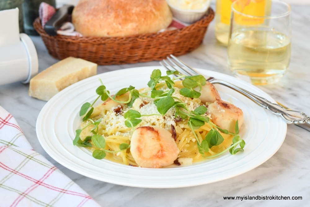 Plate of carbonara topped with seared scallops and pea shoots. Loaf of artisan bread, glass of white wine and cheese are in background