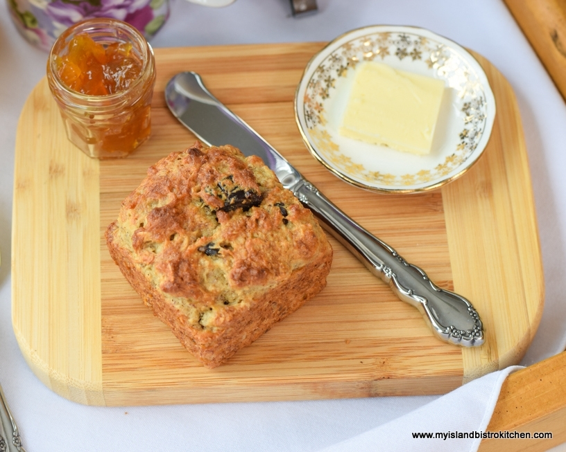 Top-down view of Gluten-free Banana Date Muffin on a wooden board with small jar of peach jam and a pat of butter
