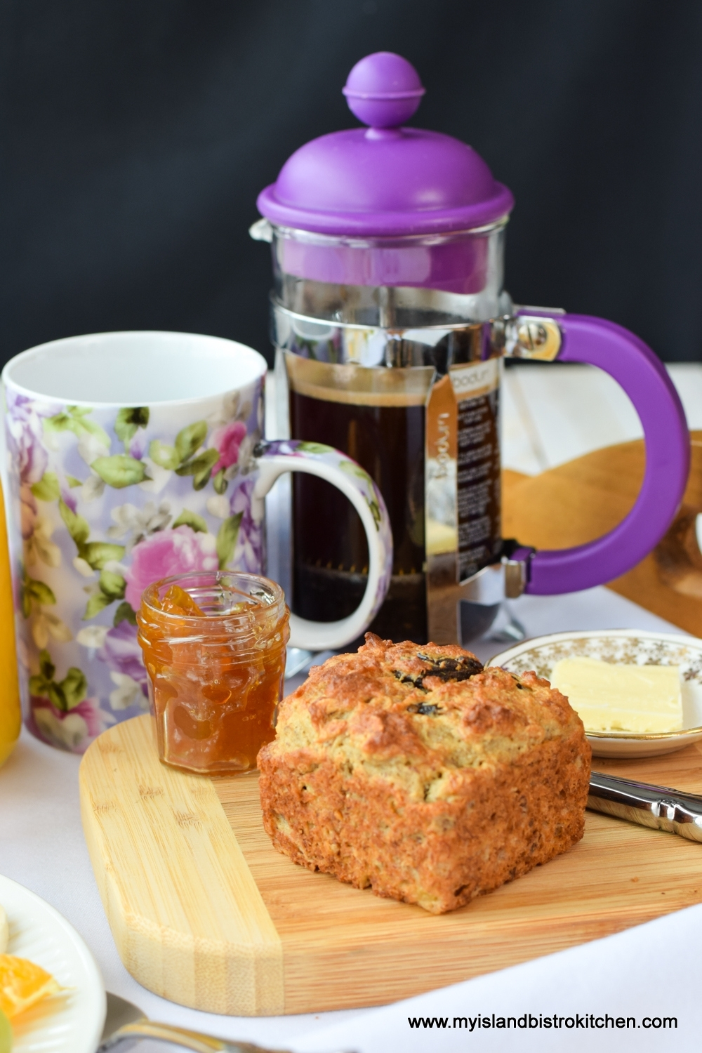 Gluten-free Banana Date Muffin on breadboard with small bottle of peach jam and pat of butter. Mauve and purple floral coffee mug and purple French press coffee maker in background