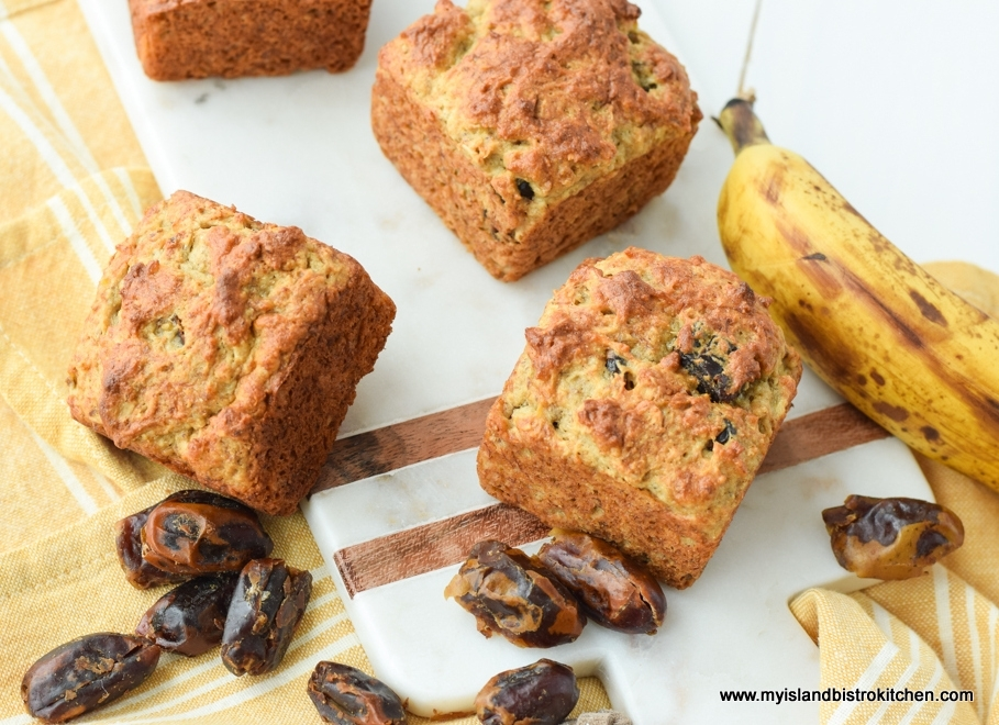 Top-down view of three Gluten-free Banana Date Muffins on marble serving board surrounded by ripe banana and dates