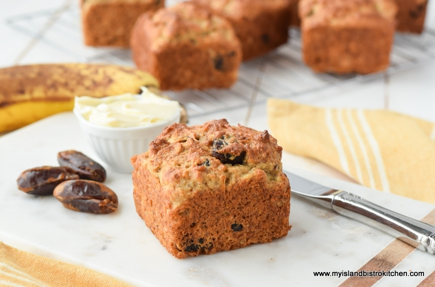 Gluten-free Banana Date Muffin on a marble serving board with muffins on a cooling rack in background