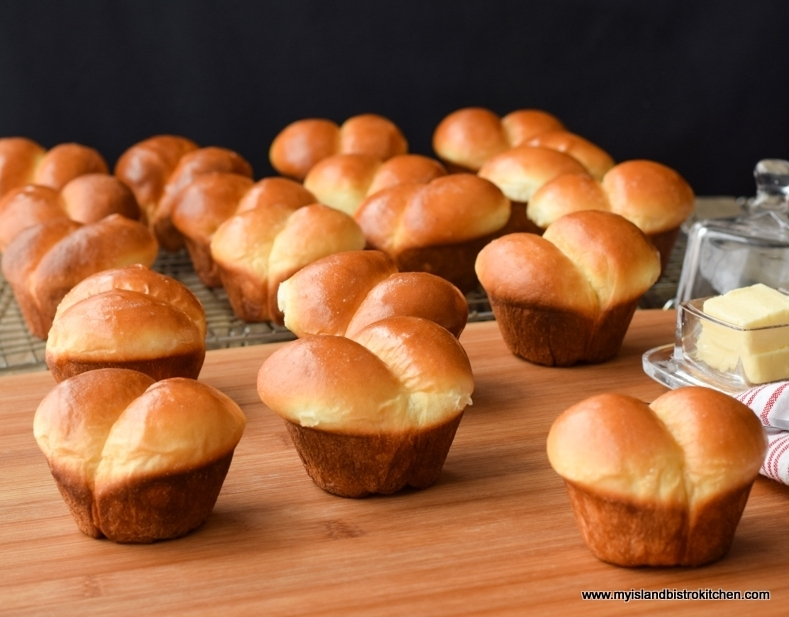 Big batch of puffy homemade dinner rolls on a bread board set against a black backdrop