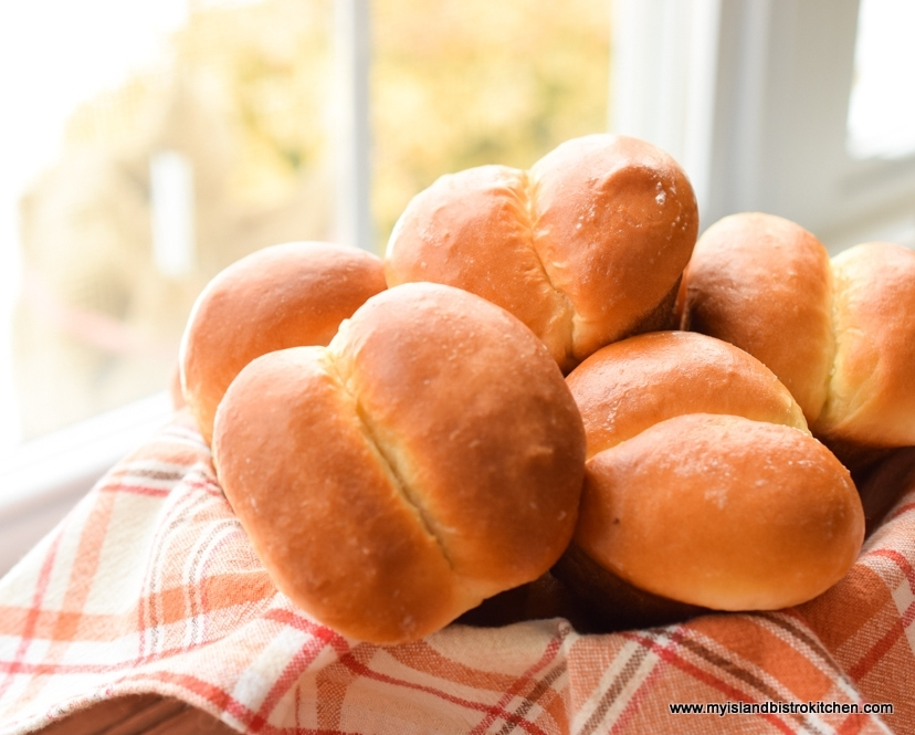 Basket of large homemade dinner rolls by a window