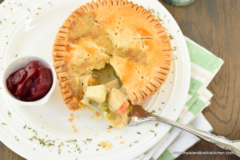 Small individual chicken pot pie on dinner plate beside small dish of cranberry sauce