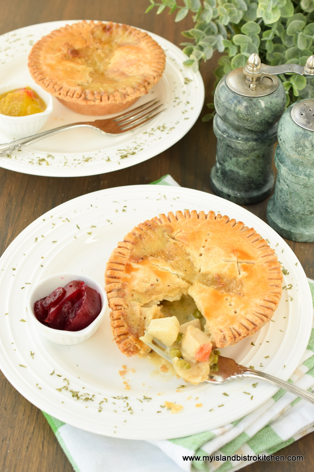 Small Chicken Pot Pie on white dinner plate with small dish of cranberry sauce