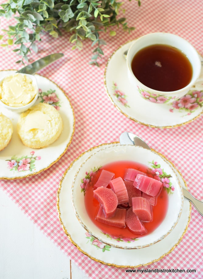 Bowl of stewed rhubarb served with homemade biscuits and a cup of tea