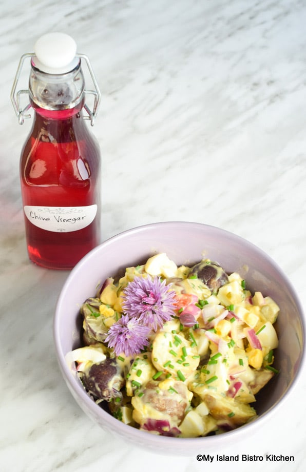 Bowl of Potato Salad with Bottle of Chive Vinegar in Background