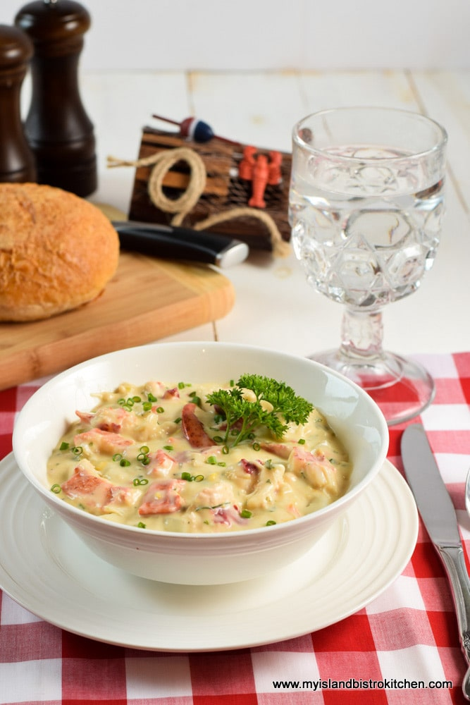 Bowl full of chowder made with lobster, potatoes, and creamed corn
