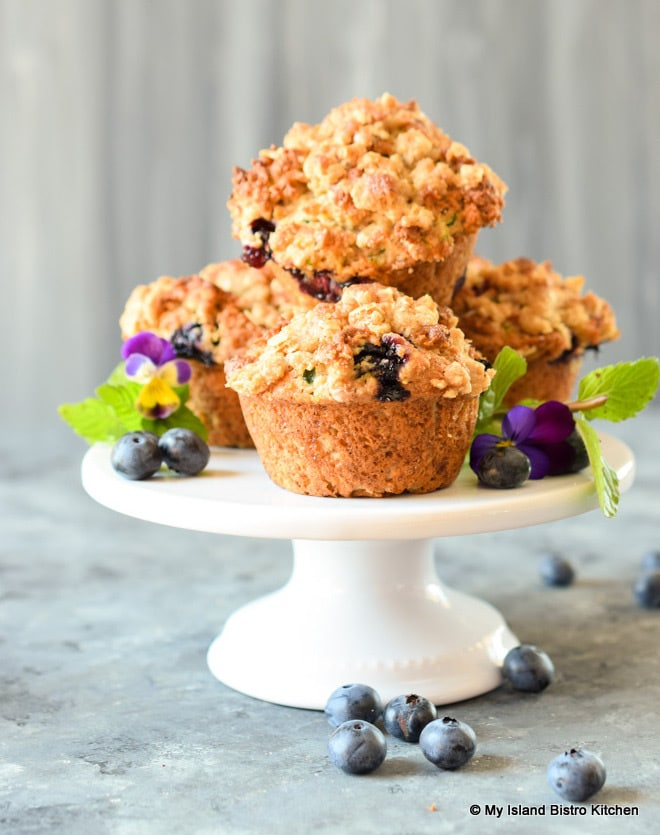 Stack of Gluten-free Blueberry Zucchini Muffins on top of white pedestal cake plate surrounded by blueberries