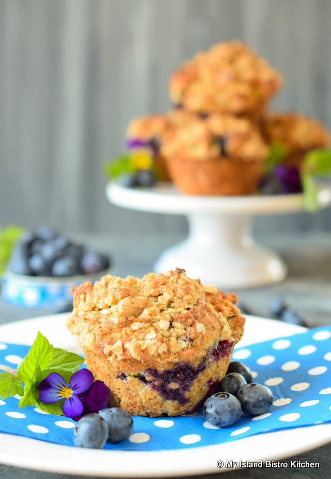 Streusel-topped Gluten-free Blueberry Zucchini Muffin on blue and white polka-dotted napkin in foreground with pedestal cake plate filled with a stack of muffins in background
