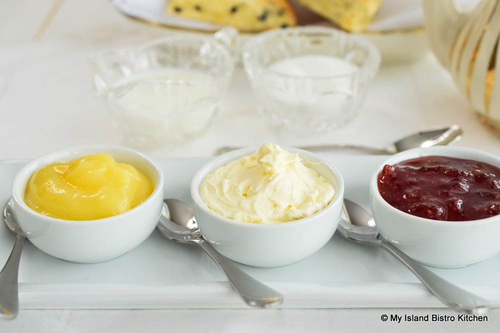 Dishes of Lemon Curd, English Double Cream, and Strawberry Jam for Scones