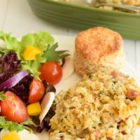 Plate of Chicken and Ham Casserole accompanied by a tossed salad and biscuit