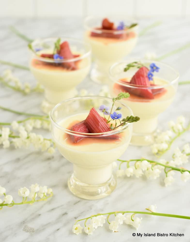 Glass dishes filled with vanilla Panna Cotta topped with Roasted Rhubarb