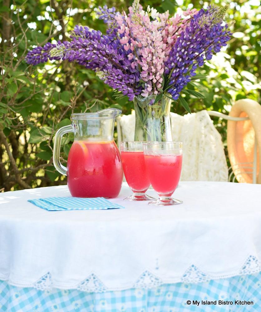 Jug and glasses of lemonade on pretty table