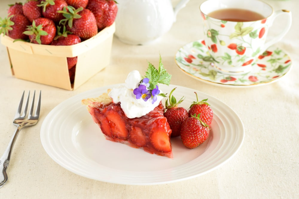 Slice of glazed strawberry pie topped with a dollop of whipped cream