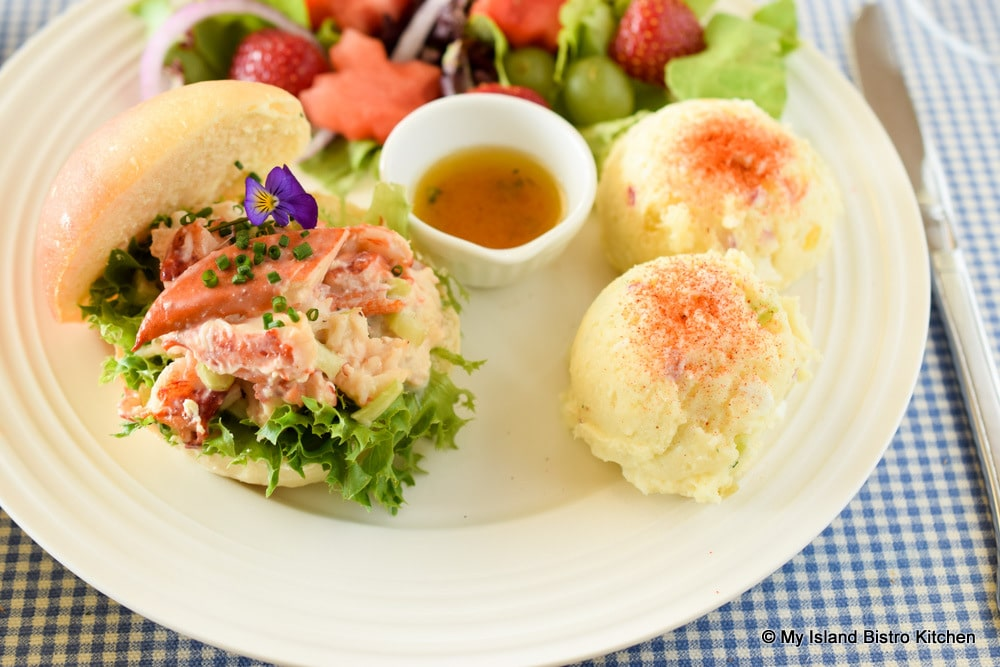 Plate filled with a PEI Lobster Roll, two scoops of potato salad with a side green salad