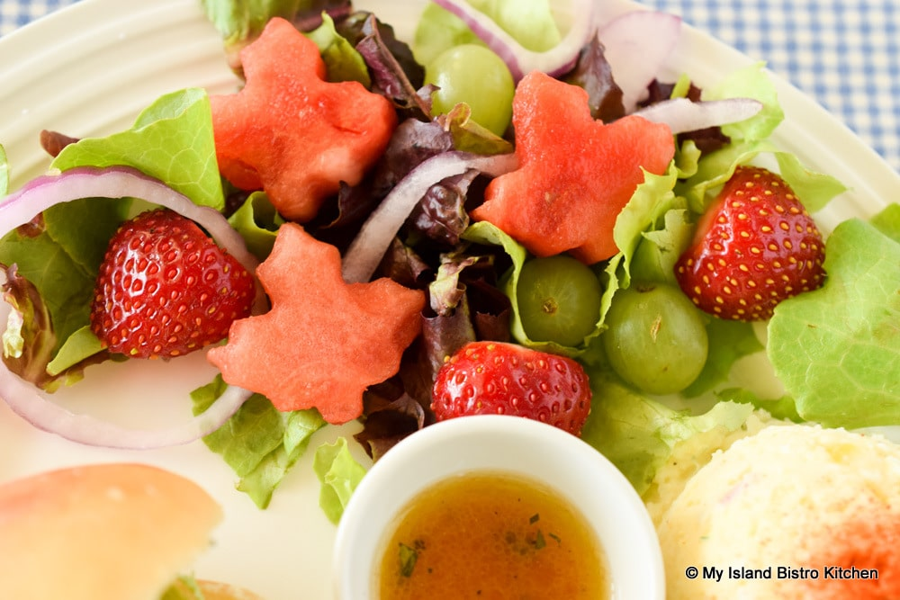 Green salad with lettuce, green grapes, red onion, strawberries, and watermelon cut in the shape of the Canadian maple leaf
