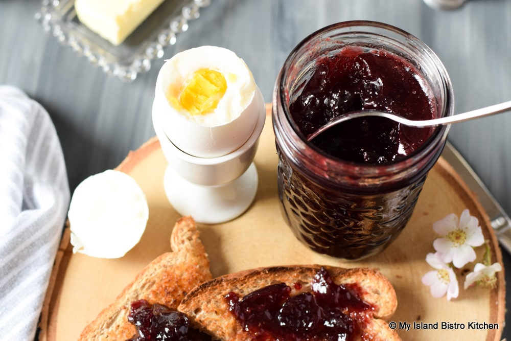 Breakfast on a board with boiled egg and toast topped with homemade cherry jam