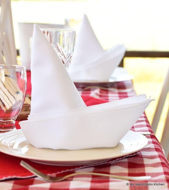 White napkins folded into sailboat shape