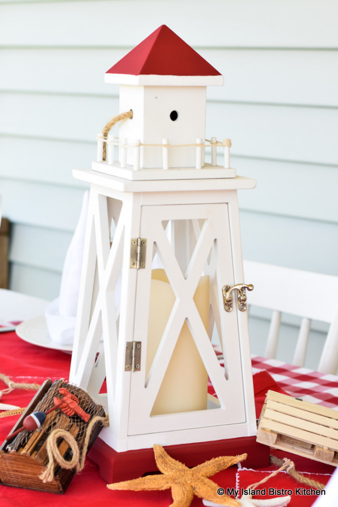 Miniature lobster traps, starfish, and seashells alongside a wooden lighthouse lantern comprise a nautical tablescape