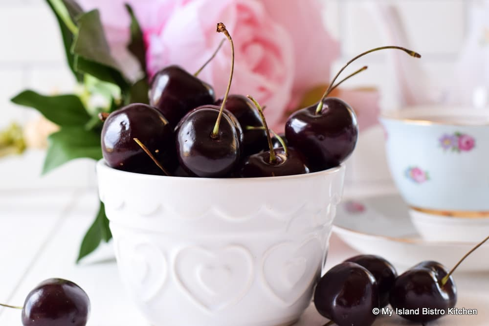 Small white bowl filled with stemmed cherries