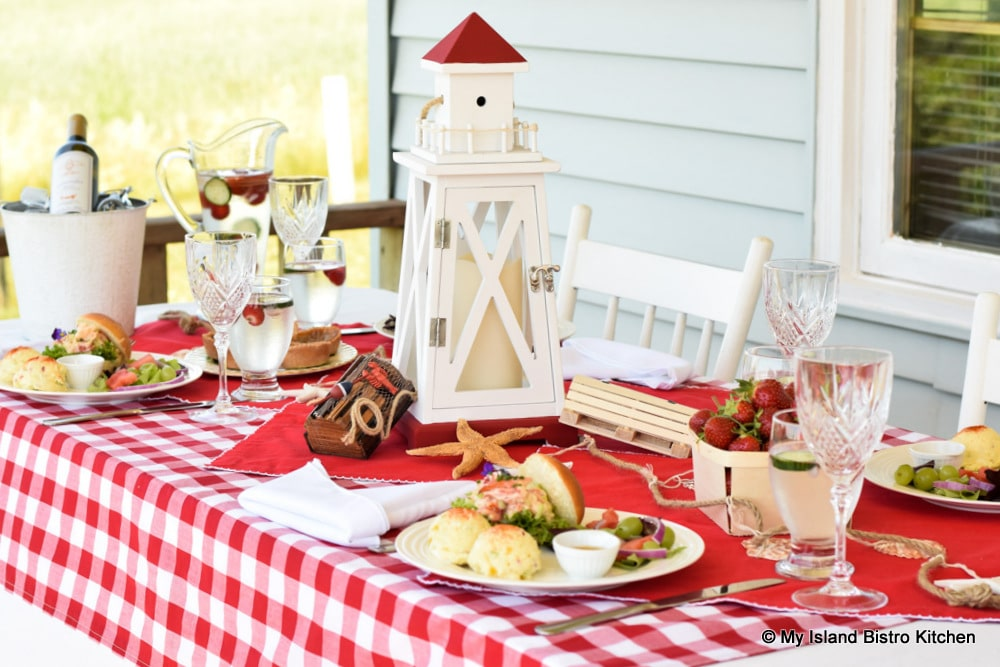 Lobster Rolls and Potato Salad on table covered with red and white checked tablecloth