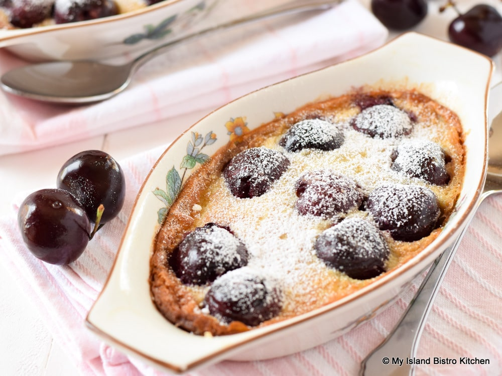 Cherry Clafoutis in au gratin dish with fresh cherries on the side