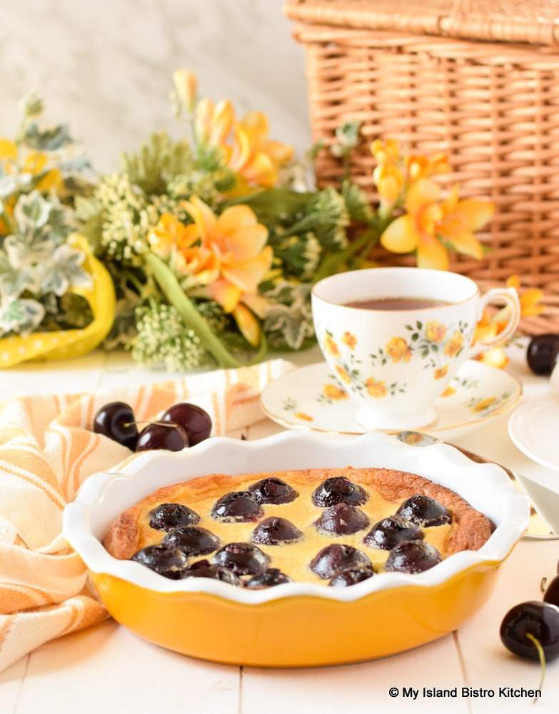Cherry Clafoutis in yellow pie plate served with a cup of tea for teatime