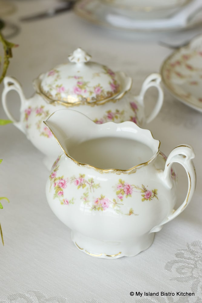 White creamer with tiny pink roses amidst pale green leaves