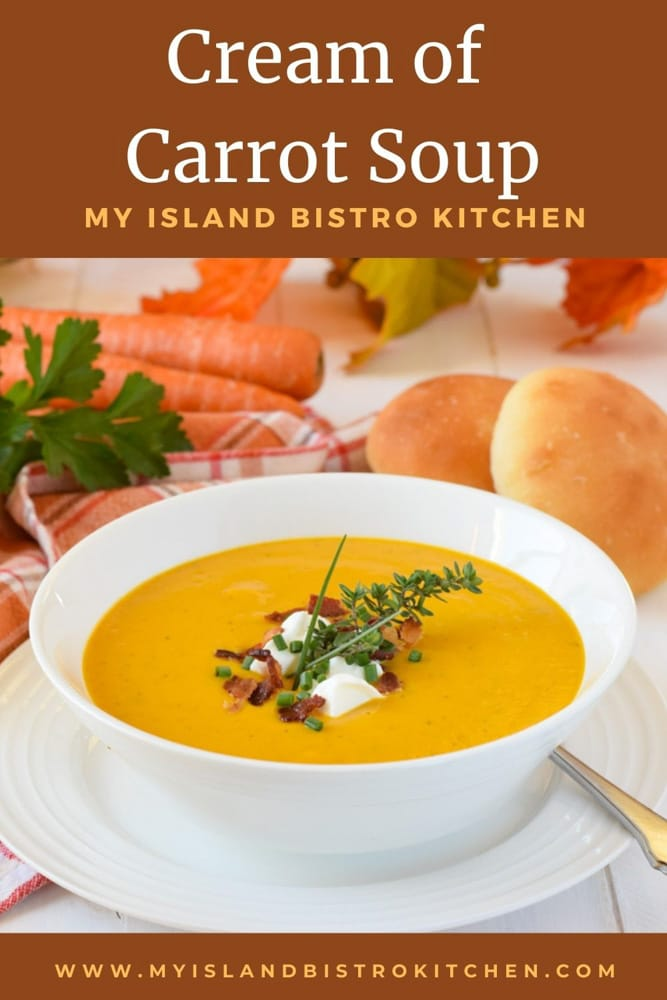 Bowl of bright golden yellow Cream of Carrot Soup garnished with a dollop of sour cream, bacon bits, and fresh herbs