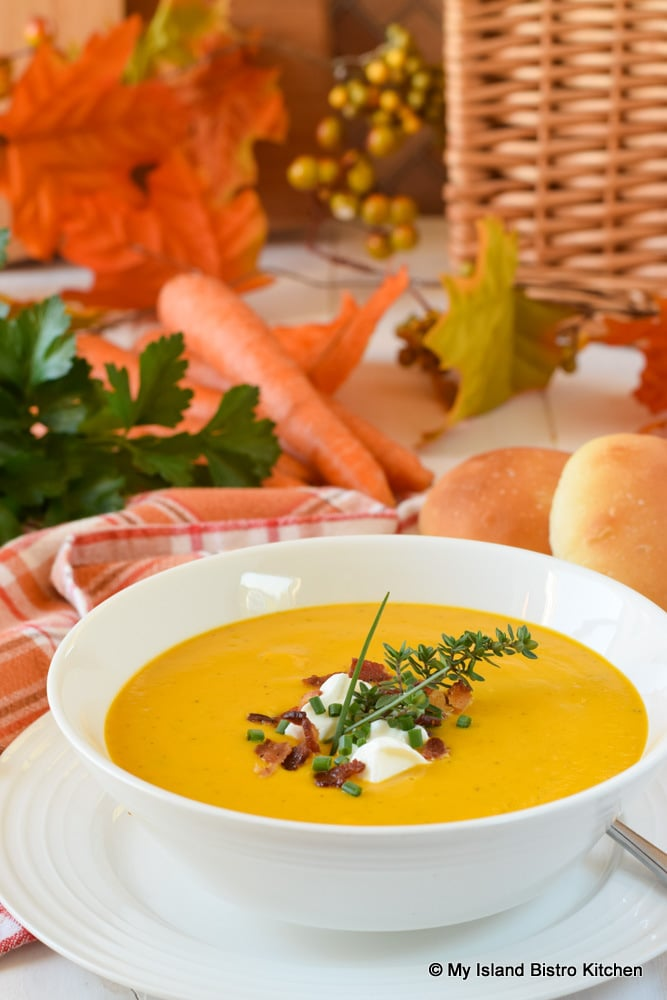 Bowl of golden yellow Cream of Carrot Soup served with homemade rolls