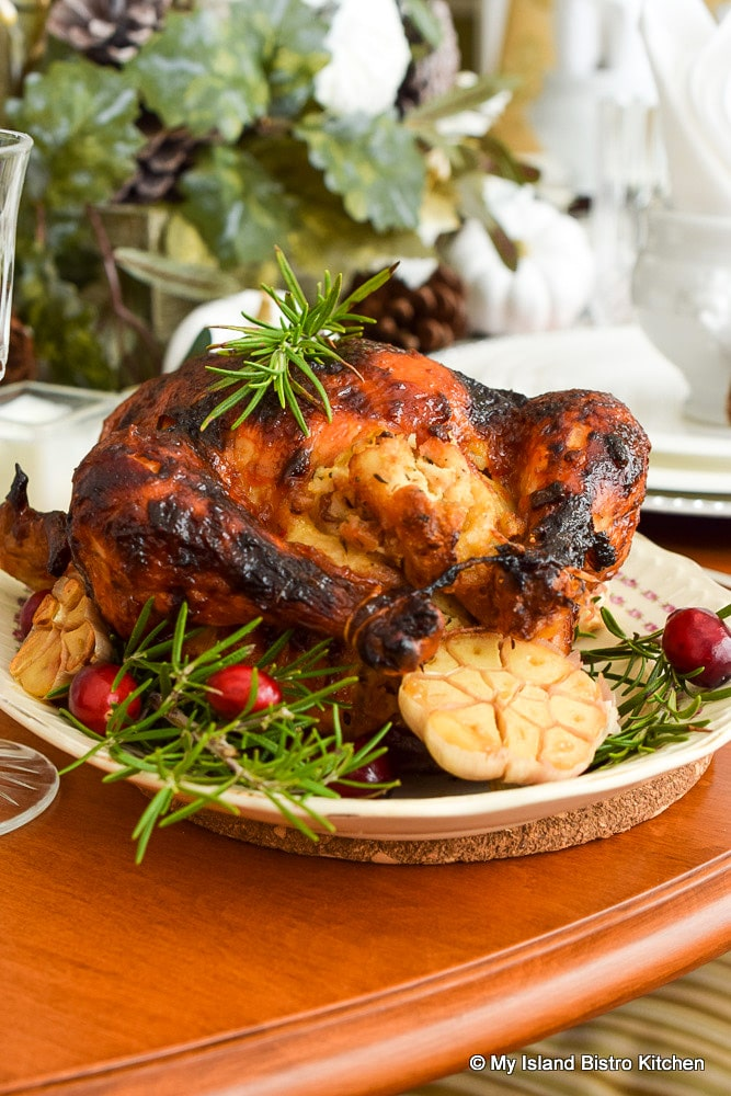Roast Chicken surrounded by roasted garlic and fresh Rosemary on oval platter