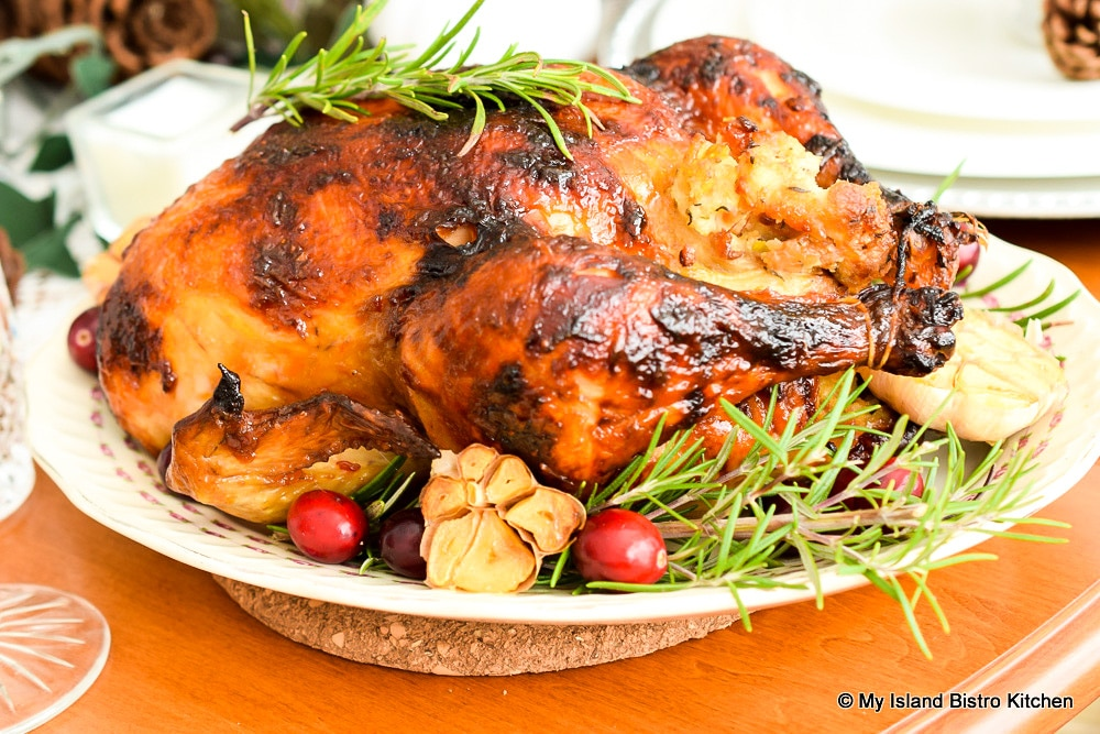 Roasted Chicken with roasted garlic and fresh Rosemary on platter