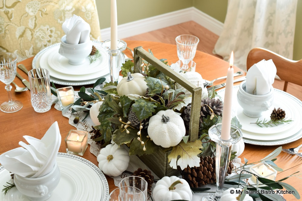 Additional small white pumpkins, pinecones, greenery, and candles surround the main floral table centerpiece