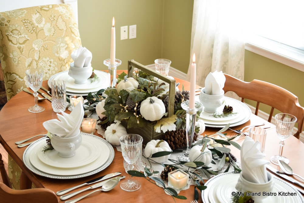 Tablesetting featuring white dinnerware and earthy toned fall centerpiece of greenery, pine cones, and tiny white pumpkins