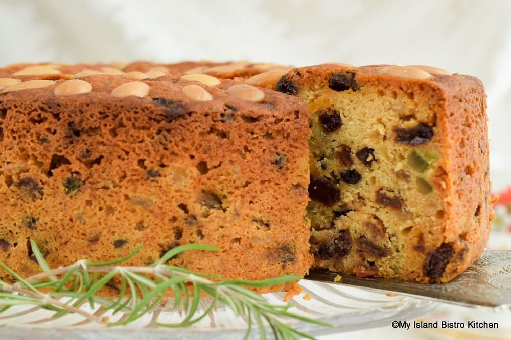 A slice of Dundee Cake studded with raisins, currants, mixed peel, and citron
